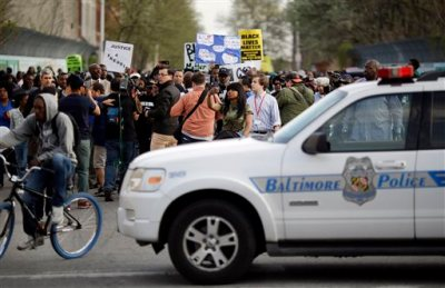 Protestors march to the site of Freddie Gray's arrest after holding a rally the Baltimore Police Department's Western District police station, Tuesday, April 21, 2015, in Baltimore. Gray died from spinal injuries a week after he was arrested and transported in a police van. (AP Photo/Patrick Semansky)