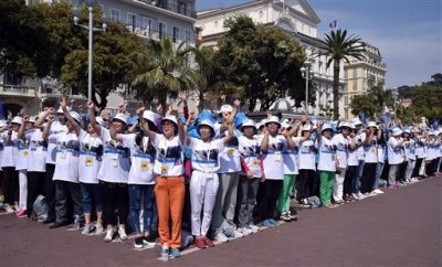 In this May 8, 2015 file photo, employees of the Tiens Group, a Chinese company which sells medicinal products, including via direct marketing, cheer as they attend a parade organized by CEO Li Jinyuan as part of a four-day celebration weekend for the 20th anniversary of his company, on the Promenade des Anglais, Nice, southeastern France. All-expenses-paid trips to reward top earners aren't unusual, but Chinese direct-sales companies are taking it to an extreme by sending thousands abroad on the same package tour. (AP Photo/Lionel Cironneau, File)