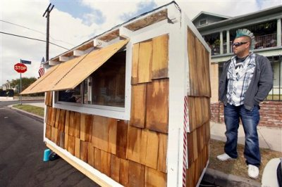 """Los Angeles resident Elvis Summers poses with his tiny house on wheels he built for a woman who had been sleeping on the streets in his South Los Angeles neighborhood on Thursday, May 7, 2015. Summers never thought more than 5.6 million people would watch a YouTube video of him constructing the 8-foot-long house for Irene """"Smokie"""" McGhee, 60, a grandmother who's been homeless for more than a decade. He estimates he spent less than $500 on plywood, shingles, a window and a door. (AP Photo/Damian Dovarganes)"""