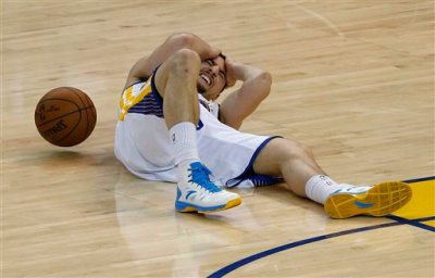 Golden State Warriors guard Klay Thompson lies on the court after being injured during the second half of Game 5 of the NBA basketball Western Conference finals against the Houston Rockets in Oakland, Calif., Wednesday, May 27, 2015. (AP Photo/Tony Avelar)