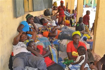Nigeria refugees rest after being deported by Niger troops arrive in Gaidam, Nigeria Thursday, May 6, 2015. Niger troops have deported more than 3,000 Nigerian fishermen and refugees escaping Boko Haram, forcing them to undertake a brutal three-day trek in which at least a dozen people died, an official and witnesses said Wednesday. Nigeria's National Emergency Management Agency's Charles Otegbabe said it was alerted by Niger and sent trucks to collect the exhausted refugees at the border, registering at least 3,000 new arrivals in Gaidam town and expect hundreds more. (AP Photo/Jossy Ola)
