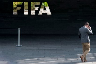 "A man walks next to the FIFA logo at the FIFA headquarters in Zurich, Switzerland, Wednesday morning, May 27, 2015. Swiss federal prosecutors say they have opened criminal proceedings related to the awarding of the 2018 and 2022 World Cups. The prosecutors' office says the proceedings are against ""persons unknown on suspicion of criminal mismanagement and of money laundering"" in connection with the votes won by Russia and Qatar. (Ennio Leanza/Keystone via AP)"