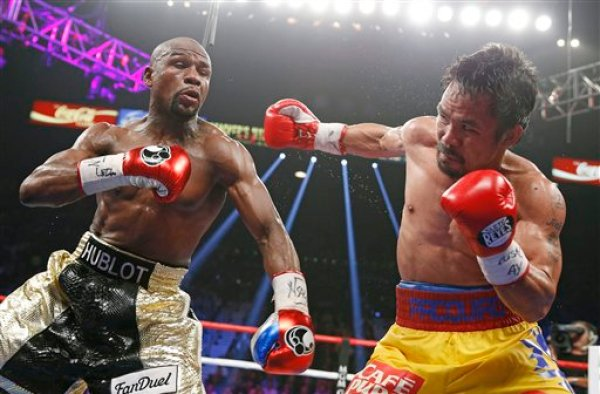 Manny Pacquiao, from the Philippines, right, throws a right against Floyd Mayweather Jr., during their welterweight title fight on Saturday, May 2, 2015 in Las Vegas. (AP Photo/John Locher)