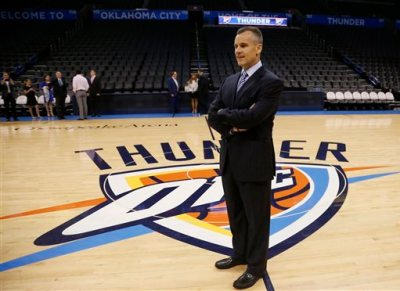 Billy Donovan, newly named head coach of the NBA Oklahoma City Thunder, poses for a photo on the Thunder logo prior to a news conference in Oklahoma City, Friday, May 1, 2015. (AP Photo/Sue Ogrocki)