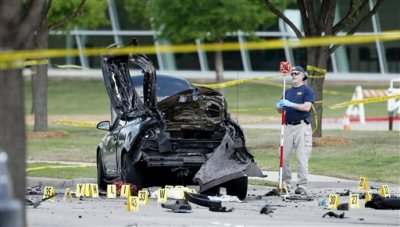 An FBI crime scene investigator documents evidence outside the Curtis Culwell Center, Monday, May 4, 2015, in Garland, Texas. Two men opened fire with assault weapons on police Sunday night who were guarding a contest for Muslim Prophet Muhammed cartoons. A police officer returned fire killing both men. (AP Photo/Brandon Wade)