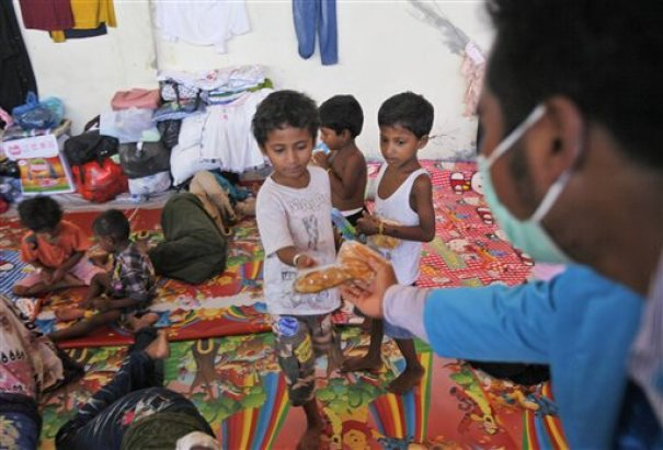 An Acehnese man hands out bread to ethnic Rohingya children at a temporary shelter in Langsa, Aceh province, Indonesia, Monday, May 18, 2015. Boatloads of more than 2,000 migrants — ethnic Rohingya Muslims fleeing persecution in Myanmar and Bangladeshis trying to escape poverty — have landed in Indonesia, Malaysia and Thailand in recent weeks. Aid groups estimate that thousands more are stranded at sea after a crackdown on human traffickers prompted captains and smugglers to abandon their human cargo. (AP Photo/Binsar Bakkara)
