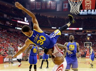 Golden State Warriors guard Stephen Curry (30) topples over Houston Rockets forward Trevor Ariza (1) during the first half in Game 4 of the Western Conference finals of the NBA basketball playoffs, Monday, May 25, 2015, in Houston. (AP Photo/David J. Phillip)