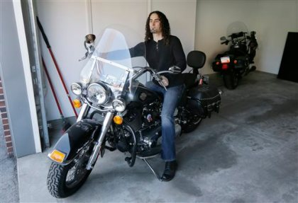 In this April 24, 2015 photo, Eugene Gualtieri, a 41-year-old lab technician at the Detroit Medical Center, prepares to ride his motorcycle in Detroit. Gualtieri took advantage of an incentive program, Live Midtown, offered by his employer and several others in the Midtown neighborhood, which allowed him to take out a $20,000 home loan that he won't have to repay if he stays in his condo for five years. In Detroit it's cheap housing and incentive programs that are partly fueling the regrowth of the Motor City's white population. (AP Photo/Carlos Osorio)