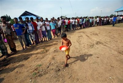 An ethnic Rohingya boy carries a plate in his hands as he walks past migrants queuing up for their meals during breakfast time at a temporary shelter in Lapang, Aceh province, Indonesia, Thursday, May 14, 2015. More than 1,600 migrants and refugees from Myanmar and Bangladesh have landed on the shores of Malaysia and Indonesia in the past week and thousands more are believed to have been abandoned at sea, floating on boats with little or no food after traffickers literally jumped ship fearing a crackdown. (AP Photo/Binsar Bakkara)