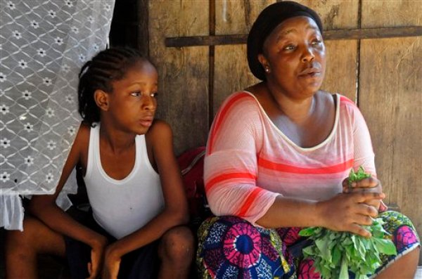 In this photo taken on Friday, May 8, 2015, Mercy Kennedy, left, sits with her caregiver  Martu Weefor, right, after school at her home in Monrovia, Liberia. On the day Mercy Kennedy lost her mother to Ebola, it was hard to imagine a time Liberia would be free of one of the world's deadliest viruses. It had swept through the 9-year-old's neighborhood, killing people house by house. Now seven months later, Liberia on Saturday officially marked the end of the epidemic that claimed more than 4,700 lives here, and Mercy is thriving in the care of a family friend not far from where she used to live. (AP Photo/ Abbas Dulleh)