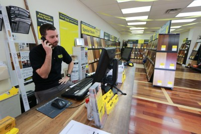 """Kiel Skrobacz, an assistant store manager at Lumber Liquidators in Lutz, Fla., speaks on the phone on Thursday, March 12, 2015. A """"60 Minutes"""" expose reported the company's Chinese-made laminate flooring contained high levels of formaldehyde, a carcinogen. The founder and chairman of the company said Friday that the retailer currently has no plans to stop selling laminate flooring made in China, even as it continues to face fallout from the report that questioned the safety of such laminates. (AP Photo/Tampa Bay Times, Rachel Crosby)"""