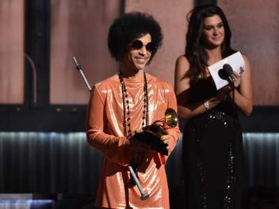 """In this Feb. 8, 2015 file photo, Prince presents the award for album of the year at the 57th annual Grammy Awards in Los Angeles. Prince has announced plans to perform at a concert in Baltimore following recent unrest in the city over the death of a man who was fatally injured in police custody. A statement issued Tuesday, May 5, 2015, says the pop icon will perform Sunday, May 10, at """"Rally 4 Peace,"""" a concert at the Royal Farms Arena in Baltimore. (Photo by John Shearer/Invision/AP)"""