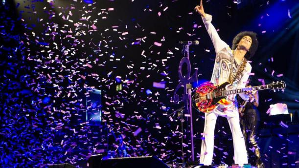 "In this 2014 photo released by NPG Records, Prince performs in Birmingham, England. On Tuesday, Sept. 30, 2014, Prince will release his first album in four years, ""Art Official Age,"" along with music from his latest protege act, 3RDEYEGIRL, ""PLECTRUMELECTRUM."" (AP Photo/NPG Records)"