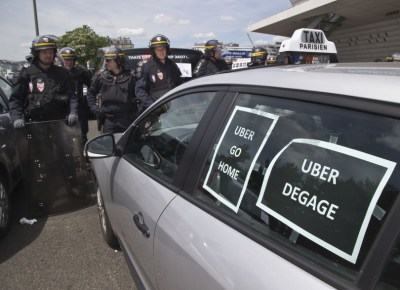 "Riot police officers stand next to a cab with posters which reads, ""Uber go home"" and ""Uber get out out,"" during a taxi drivers demonstration in Paris, France, Thursday, June 25, 2015. (Michel Euler/AP)"