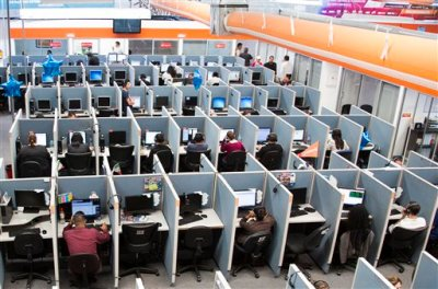 In this Aug. 13, 2014 photo, workers sit at desks at  Firstkontact Center, a call center in the northern border city of Tijuana, Mexico. If you're sitting in an office, you should probably read this standing up. In the first advice of its kind, British experts are recommending office workers stand for at least two hours a day, in a warning against the dangers of sitting. The guidelines were developed by a group of experts invited by Public Health England and an advocacy group and were published online Monday, June 1, 2015 in the British Journal of Sports Medicine. (AP Photo/Alex Cossio, File)