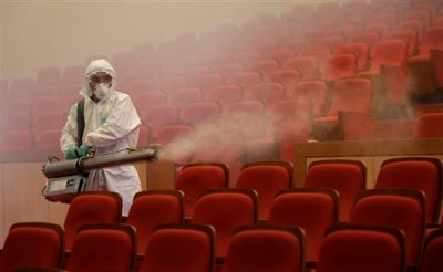 A worker wearing protective gears sprays antiseptic solution as a precaution against the spread of MERS, Middle East Respiratory Syndrome, virus at an art hall in Seoul, South Korea, Friday, June 12, 2015. The outbreak of Middle East respiratory syndrome has caused panic in South Korea. (AP Photo/Lee Jin-man)
