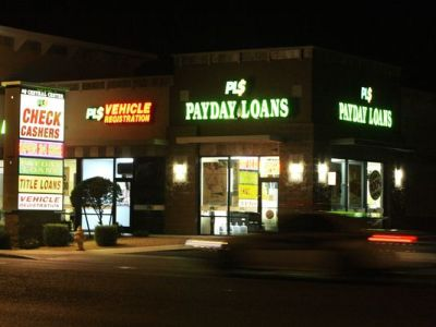 Neon signs illuminate a payday loan business. Payday loan borrowers often roll over their loans and wind up paying more in fees than they borrowed, the Consumer Financial Protection Bureau warns in a report out in March. (Ross D. Franklin/AP Photo)