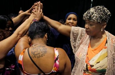 In this July 8, 2015 file photo, Gwen Carr, mother of Eric Garner, right, joins women whose families members were killed by police officers after New York Gov. Andrew Cuomo signed an executive order that puts the office of the state attorney general in charge of investigating killings by police. New York City reached a settlement Monday, July 13 with the family of Garner for about $5.9 million, almost a year after the 43-year-old died in police custody. (AP Photo/Seth Wenig, File)