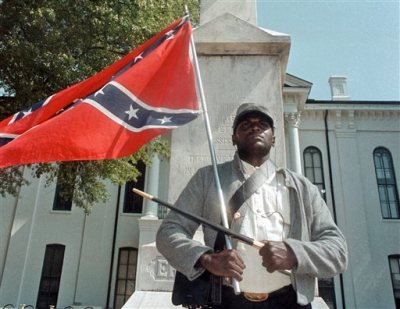 In this May 8, 2000, file photograph, Anthony Hervey holds a Confederate flag while standing underneath the Confederate monument in Oxford, Miss. The Highway Patrol says 49-year-old Hervey was killed Sunday, July 19, 2015, when his 2005 Ford Explorer left the roadway and overturned on Mississippi Highway 6 in Lafayette County. Hervey, of Oxford, has drawn attention over the years for opposing efforts to change the flag. He said he dressed in Rebel soldier garb to honor blacks who served with the Confederacy during the Civil War. (Bruce Newman/The Oxford Eagle via AP, File)