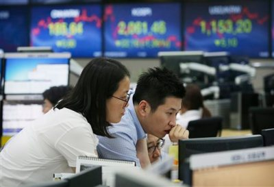 Currency traders watch monitors at the foreign exchange dealing room of the Korea Exchange Bank headquarters in Seoul, South Korea, Wednesday, July 22, 2015.  Asian stock markets dropped Wednesday after U.S. earnings fell short of expectations and investors began to focus on next week's Federal Reserve meeting.(AP Photo/Ahn Young-joon)