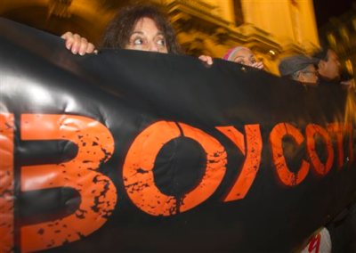 """In this Wednesday, Oct. 31, 2012 file photo, French demonstrators and supporters of Palestinians hold a placard with the word """"Boycott"""" during a demonstration in Paris, France. A campaign called BDS, which was started by Palestinian activists 10 years ago to boycott Israel, has grown into a worldwide network of thousands of volunteers lobbying corporations, artists and academic institutions to sever ties with Israel. (AP Photo/Jacques Brinon, File)"""