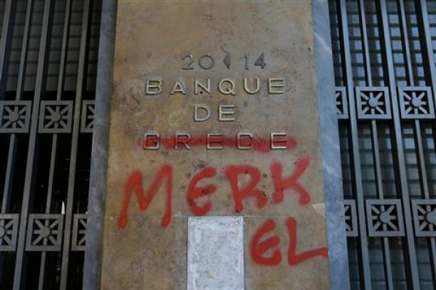Red spray paint covers a French-language Bank of Greece sign to read 'Bank of Merkel' in reference to German Chancellor Angela Merkel in Athens, Monday, July 6, 2015. Greek Finance Minister Yanis Varoufakis resigned Monday, saying he was told shortly after Greece's decisive referendum result that some other eurozone finance ministers and the country's other creditors would appreciate his not attending the ministers' meetings. (AP Photo/Thanassis Stavrakis)
