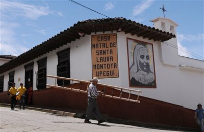 In this May 10, 2013 file photo, a man carries a ladder past the home where Mother Laura Montoya or Madre Laura, was born in Jerico, Colombia. The planned July 29, 2015 debut of a TV soap opera dramatizing the life of Madre Laura, Colombia's only Roman Catholic saint, is shrouded in controversy after devotees of the missionary nun filed a lawsuit seeking to correct what they say is an unseemly depiction. The Congregation of Missionaries of Mary Immaculate and St. Catherine of Sienna, the order founded by Montoya, says that despite repeated requests it was never consulted by producer Caracol about the script. The group questions the network's right to use Montoya's name and image, whose copyright it claims. (AP Photo/Luis Benavides, File)