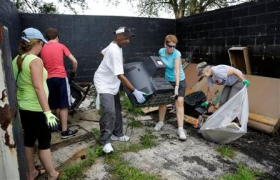 Volunteers help to cleanup trash behind a business Monday, July 27, 2015, in Ferguson, Mo. Hundreds of volunteers converged Monday morning on West Florissant Avenue for a litter-pickup and weeding effort spearheaded by a local radio station ahead of the Aug. 9 one-year anniversary of Michael Brown's death. It's one of the areas hardest hit by last year's unrest in Ferguson that followed the police shooting death of Brown. (AP Photo/Jeff Roberson)