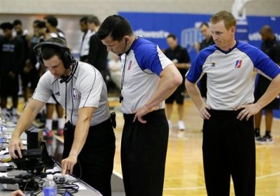 Officials Kevin Scott, from left, Andy O'Brien and Rusty Phillips look over a replay monitor during the first half of an NBA summer league basketball game between the Orlando Magic Blue and the Memphis Grizzlies , Tuesday, July 7, 2015, in Orlando, Fla. (AP Photo/John Raoux)