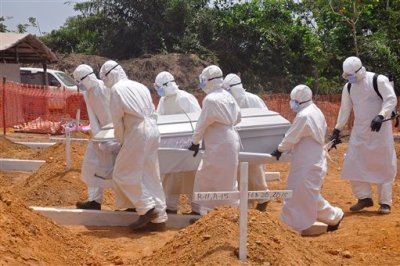 In this file photo taken on Wednesday, March 11, 2015,  health workers carry a body of a person that they suspected died form the Ebola virus at a new graveyard on the outskirts of Monrovia, Liberia. The corpse of a 17-year-old man has tested positive for Ebola in Liberia, but no other cases have been reported, the country's deputy health minister said late Monday, June 29, 2015.  (AP Photo/ Abbas Dulleh,File)