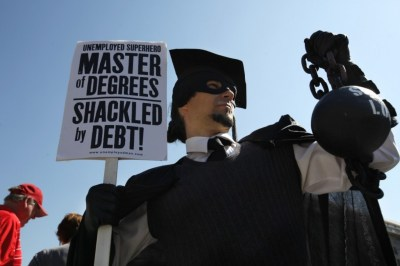 """In this Oct. 6, 2011 photo, Gan Golan of Los Angeles, dressed as the """"Master of Degrees,"""" holds a ball and chain representing his college loan debt during Occupy DC activities in (AP Photo/Jacquelyn Martin)"""
