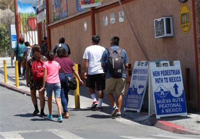 In this Aug. 18, 2015, photo, a group of people follow the new signs indicating the direction to the new pedestrian path to the Mexico border crossing in San Ysidro, Calif.  Starting late Wednesday, Aug. 19, pedestrians going to Tijuana from San Diego at the San Ysidro crossing must choose between a line for Mexicans who get waved through, and a line for foreigners. Foreigners must show a passport, fill out a form and - if staying more than a week - pay for a six-month permit. (AP Photo/Lenny Ignelzi)