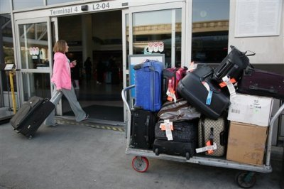 In this March 27, 2014 file photo, a baggage cart sits outside a terminal at Los Angeles International Airport in Los Angeles. A Senate committee report urges the Transportation Department to crack down on unfair or hidden airline fees for things like seat reservations, checked baggage and ticket changes or cancellations. The report is on an investigation by the Democratic staff of the Senate Commerce Committee. It says there appears to be no justification for checked bag fees other than increased profit. The report recommends that any bag fees be tied to actual costs incurred by an airline.  (AP Photo/Nick Ut, File)