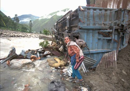 In this Jan. 15, 1998 file photo, a women sifts through rubble near her destroyed home after much of the town of Santa Teresa in Cuzco, was destroyed by a mudslide brought on by persistent rains attributed El Nino.  (AP Photo/Oscar Paredes, File)