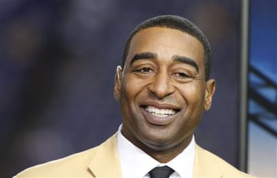 """This is a Nov. 7, 2013, file photo showing Cris Carter smiling in the NFL booth during the first half of an NFL football game between the Minnesota Vikings and Washington Redskins in Minneapolis. Hall of Fame receiver Cris Carter has issued an apology for telling NFL rookies at a league symposium in 2014 that they should """"get a fall guy"""" to help them avoid trouble. Carter posted his apology on Twitter after an ESPN article drew attention to the remarks he made during a presentation last year. (AP Photo/Ann Heisenfelt, File)"""
