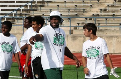 In this photo taken July 11, 2015, former Pflugerville High School football standout IK Enemkpali, center, gives directions before a drill at his annual football camp at Kuempel Stadium in Pflugerville, Texas. Enemkpali, an outside linebacker in his second season, was immediately released by the New York Jets after punching quarterback Geno Smith and breaking his jaw, Tuesday, Aug. 11, 2015. (Joe Harrington/Austin American-Statesman via AP)