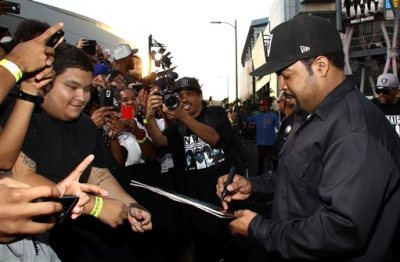 """Ice Cube signs an autographs as he arrives at the Los Angeles premiere of """"Straight Outta Compton"""" at the Microsoft Theater on Monday, Aug. 10, 2015. (Photo by John Salangsang/Invision/AP)"""