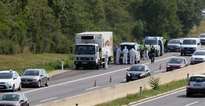 Police stands near a truck that stands on the shoulder of the highway A4 near Parndorf south of Vienna, Austria, Thursday, Aug 27, 2015. At least 20 migrants were found dead in the truck parked on the Austrian highway leading from the Hungarian border, police said. (AP Photo/Ronald Zak)