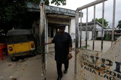 In this photo taken Saturday, Aug. 1, 2015, Felix Nwabueze, who was a quality control officer In the late 1970s at a laboratory in Nigeria where millions of smallpox vaccines were made, walk past the abandoned building in Lagos, Nigeria. International health officials are scrambling, without much success, to find meningitis C vaccines as an outbreak of the child-killing disease threatens to balloon into an epidemic. (AP Photo/Sunday Alamba)