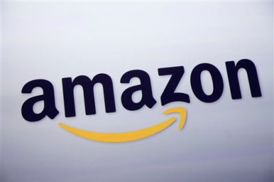 In this Sept. 28, 2011 file photo, the Amazon.com logo is displayed at a news conference in New York. The e-commerce powerhouse on Tuesday, Sept. 1, 2015 said it will now let members of its $99 annual Prime loyalty program download some shows and movies on its streaming video service to watch offline, or when there is no Internet connection available, for free. (AP Photo/Mark Lennihan, File)