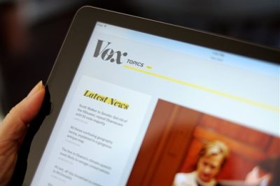The Vox website is displayed on an iPad held by an Associated Press staffer in Los Angeles, on Tuesday, Sept. 1, 2015. Comcast, which became a TV powerhouse by signing up Generation Xers, is investing in online media outlets like BuzzFeed and Vox that attract millenial viewers. (AP Photo/Richard Vogel)