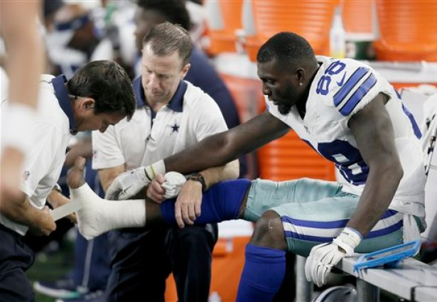Dallas Cowboys wide receiver Dez Bryant (88) is tended to on the sideline after injuring his foot during the second half of an NFL football game against the New York Giants Sunday, Sept. 13, 2015, in Arlington, Texas. (AP Photo/Brandon Wade)