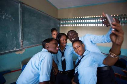 Students pose for a photo in their classroom before the start of the flag ceremony to mark the first day of the new school year at Lycee National in the Petion-Ville suburb of Port-au-Prince, Haiti, Monday, Sept. 7, 2015. (Dieu Nalio Chery/AP Photo)