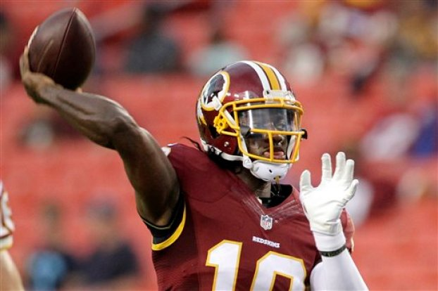 In this Aug. 20, 2015 file photo, Washington Redskins quarterback Robert Griffin III warms up before an NFL preseason football game against the Detroit Lions, in Landover, Md. Kirk Cousins will start the season as Washington's quarterback, Redskins coach Jay Gruden said Monday. With Griffin still in the NFL's concussion protocol program, Gruden opted for Cousins, who was drafted along with Griffin in 2012 and has started nine games when Griffin has been hurt, going 2-7. (AP Photo/Mark Tenally, File)