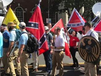 "Alt-right members preparing to enter Emancipation Park holding Nazi, Confederate, and Gadsden ""Don't Tread on Me"" flags in Charlottesville, Va. (Anthony Crider/Wikimedia Commons)"