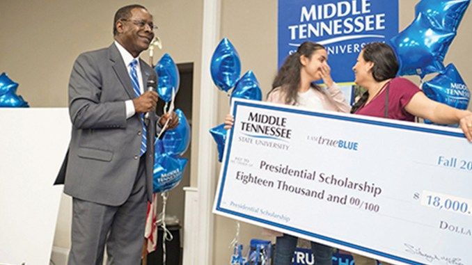 """MTSU President Sidney A. McPhee, left, delivers the """"shocking"""" news to Diana Makram and her mother, Hanan Marcos, that the Martin Luther King Jr. Magnet High School senior would receive a four-year, $18,000 Presidential Scholarship Oct. 4 during the True Blue Tour event in Nashville. MTSU photo by David Foster"""