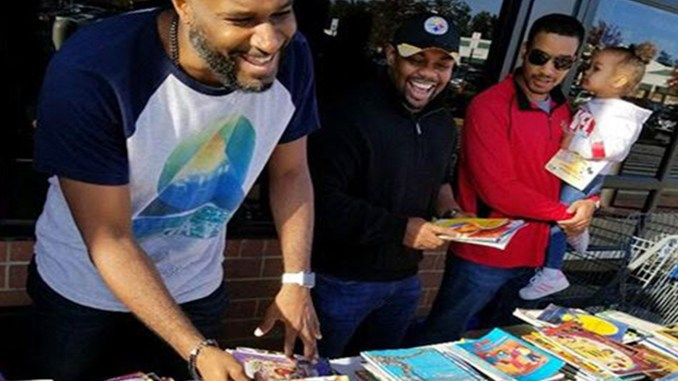 Founders of B.L.A.C.K. 2 Life distributing free books to children (Courtesy Photo)