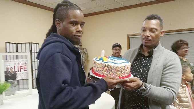 Description: Pastor Henry Lavender gives DeAndre Bramlett, who broke into Lavender's church, something Bramlett said he'd never had – a birthday cake. (Photo: Dr. Sybil C. Mitchell)