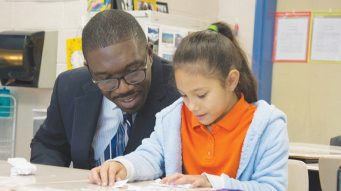 At one of his more than 400 school visits, Dr. Shawn Joseph looks on as an elementary student works on a class project.