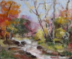 Ginger Summit landscape in felt. A bubbling stream with trees showing autumn foliage of reds and oranges.